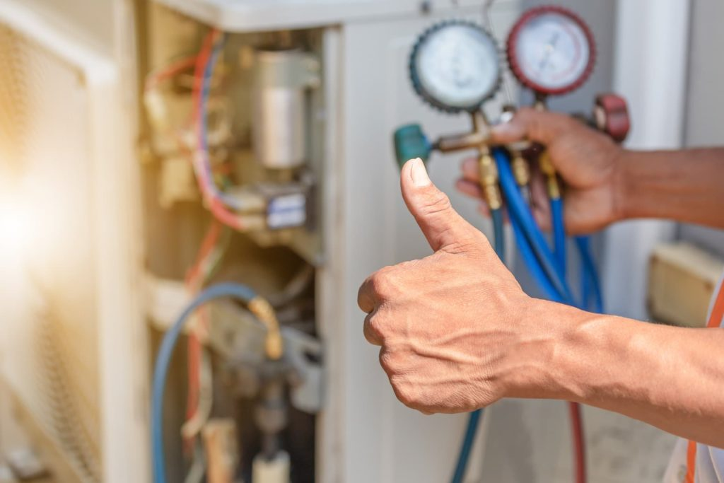 a man giving the thumb's up sign while also holding a gauge manifold