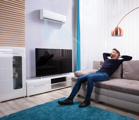 Man Relaxing On Sofa Near Air Condition