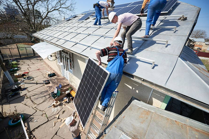 Electricians lifting blue solar module on roof